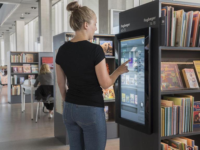Bilde av en hånd ta ut en bok fra hyllen